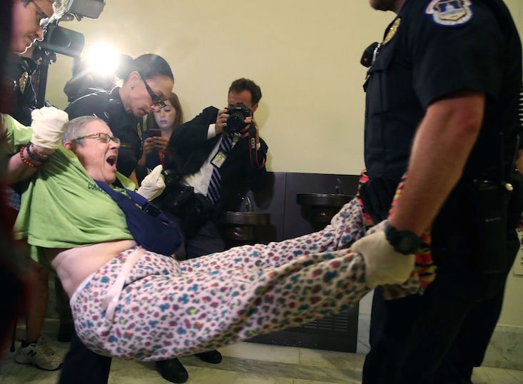 Capitol Police remove a woman participating in a disability rights protest in front of Senate Majority Leader Mitch McConnell's office. Mark Wilson/Getty Images