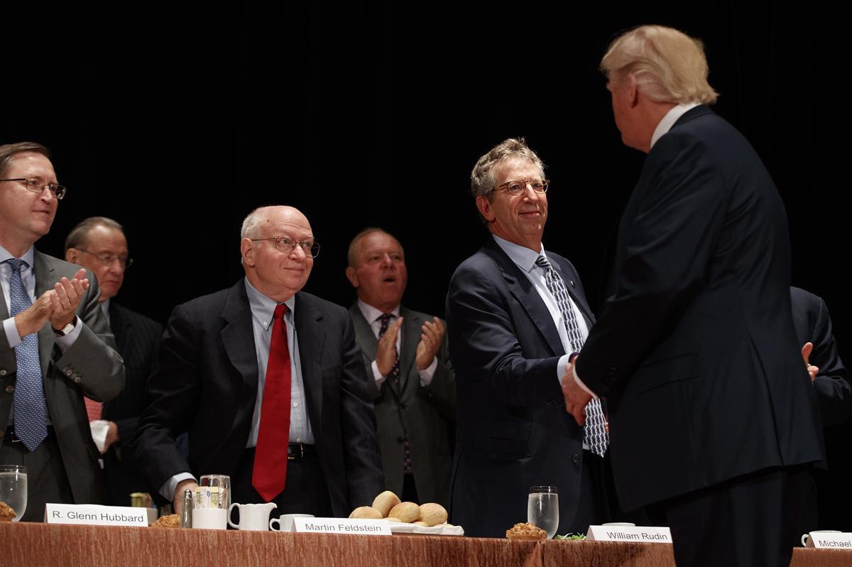 Economists, from left, R. Glenn Hubbard, left, Martin Feldstein, and William Rudin, greet then Republican presidential candidate Donald Trump as he arrives to speak at the Economic Club of New York, Thursday, Sept. 15, 2016, in New York. (AP Photo/ Evan Vucci)