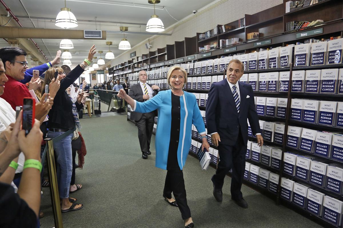 "Hillary Rodham Clinton, escorted by Leonard Riggio, chairman of Barnes and Noble, arrives to sign copies of her book ""What Happened"" at a book store in New York — Tuesday, Sept. 12, 2017 (AP Photo/Seth Wenig)"