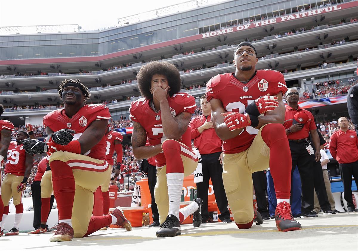 San Francisco 49ers outside linebacker Eli Harold, left, quarterback Colin Kaepernick, center, and safety Eric Reid kneel during the national anthem before an NFL football game against the Dallas Cowboys in Santa Clara, Calif., Sunday, Oct. 2, 2016. (AP Photo/Marcio JoseSanchez)