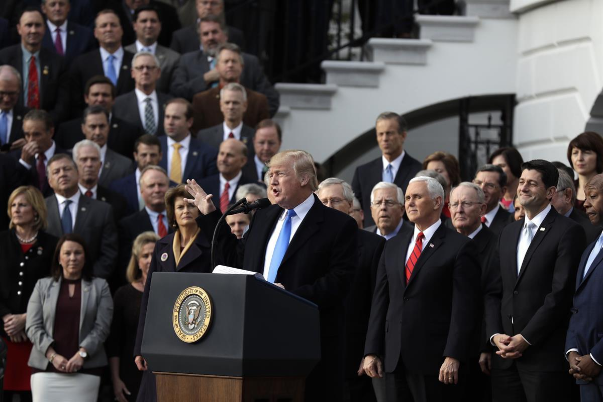 President Donald Trump, with Republican leaders behind him, speaks during the tax bill passage event on the South Lawn of the White House — Wednesday, Dec. 20, 2017 (AP Photo/Evan Vucci)