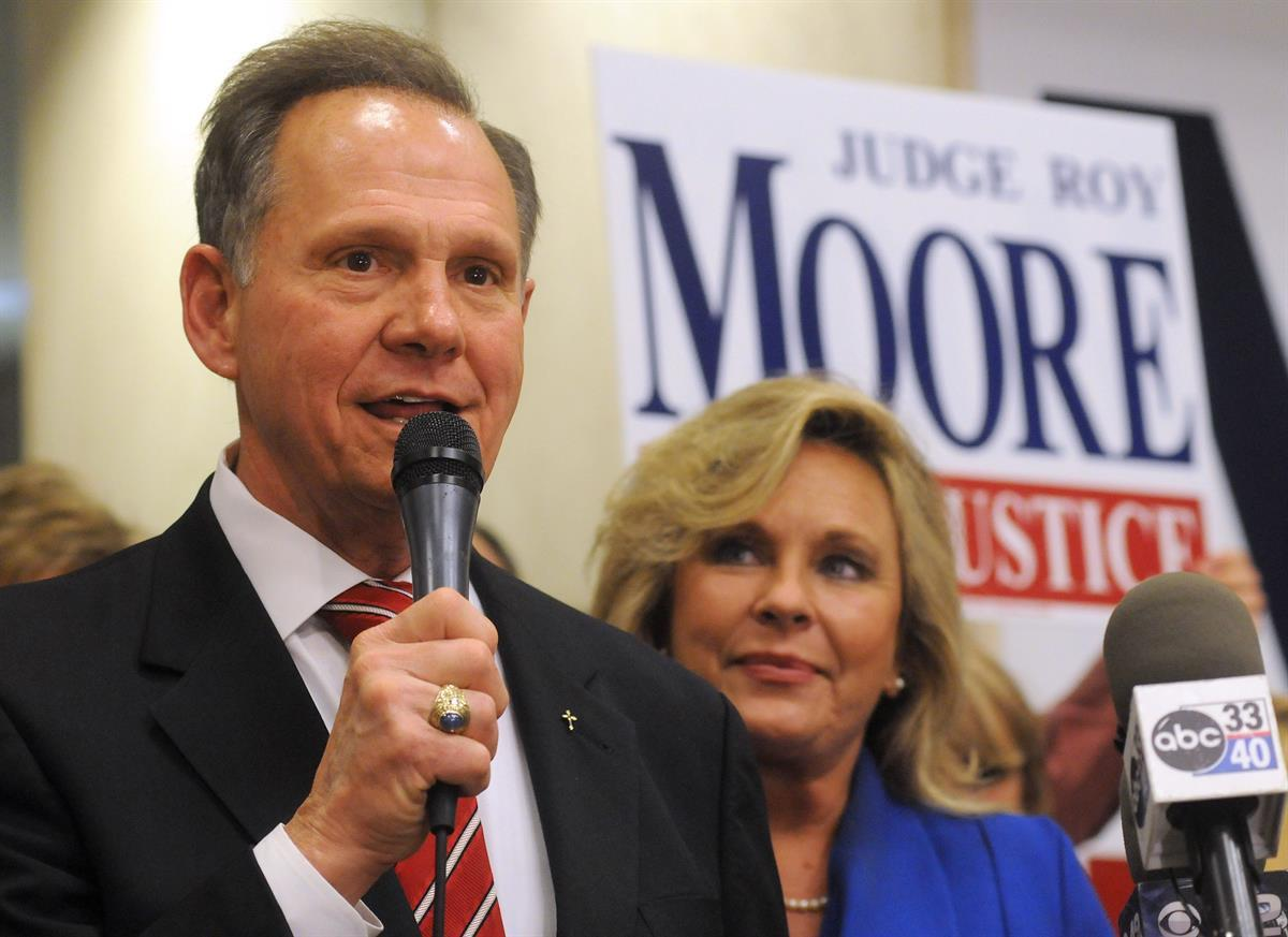 Roy Moore speaks to the audience as wife Kayla looks on at his election party in Montgomery, Ala., on election night — Nov. 6, 2012 (AP Photo/David Bundy, File)