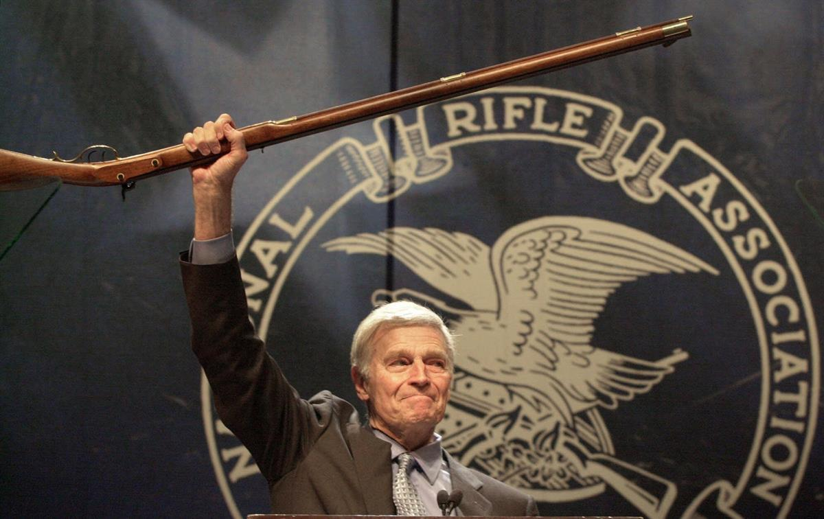 NRA president Charlton Heston holds up a musket as he tells the 5000 plus members attending the 129th Annual Meeting & Exhibit in Charlotte, NC—May 20, 2000 (AP Photo/Ric Feld)