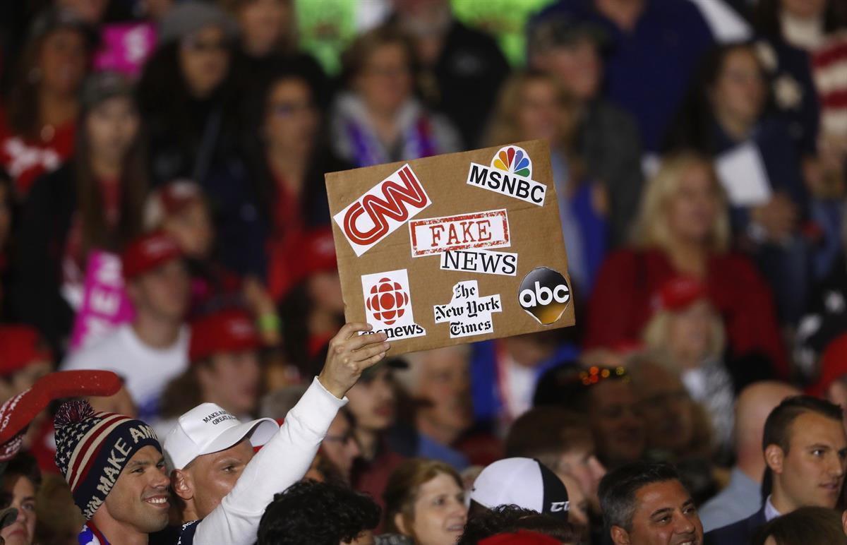 An audience member holds a fake news sign during a President Donald Trump campaign rally in Washington Township, Michigan, Saturday, April 28, 2018. (AP Photo/Paul Sancya)