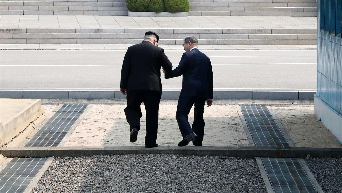 Kim Jong Un, left, and Moon Jae-in, hold hands as they cross the Military Demarcation Line in Paju. (Source: Inter-Korean Summit Press Corps/Pool via Bloomberg)