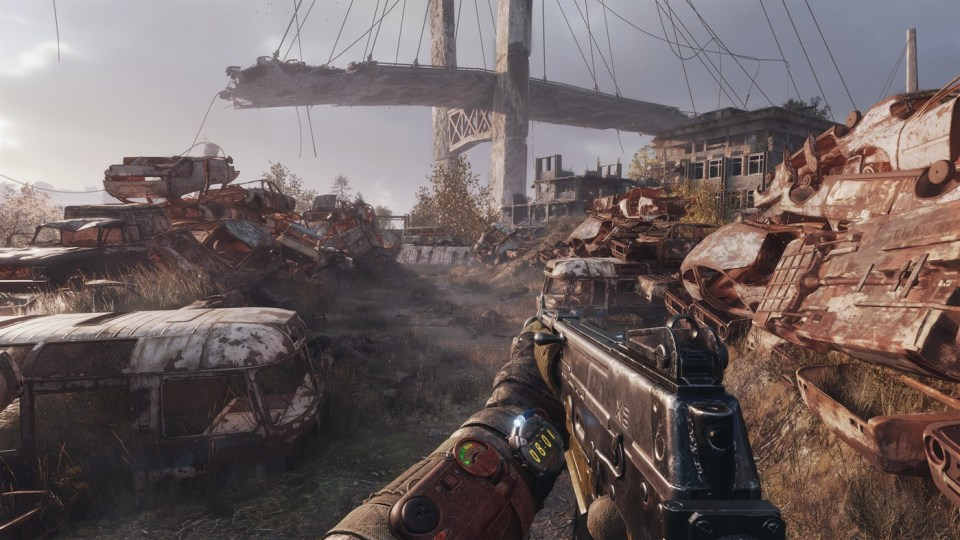 A first person view of your character holding a gun in a rusty junkyard, looking at a destroyed suspension bridge