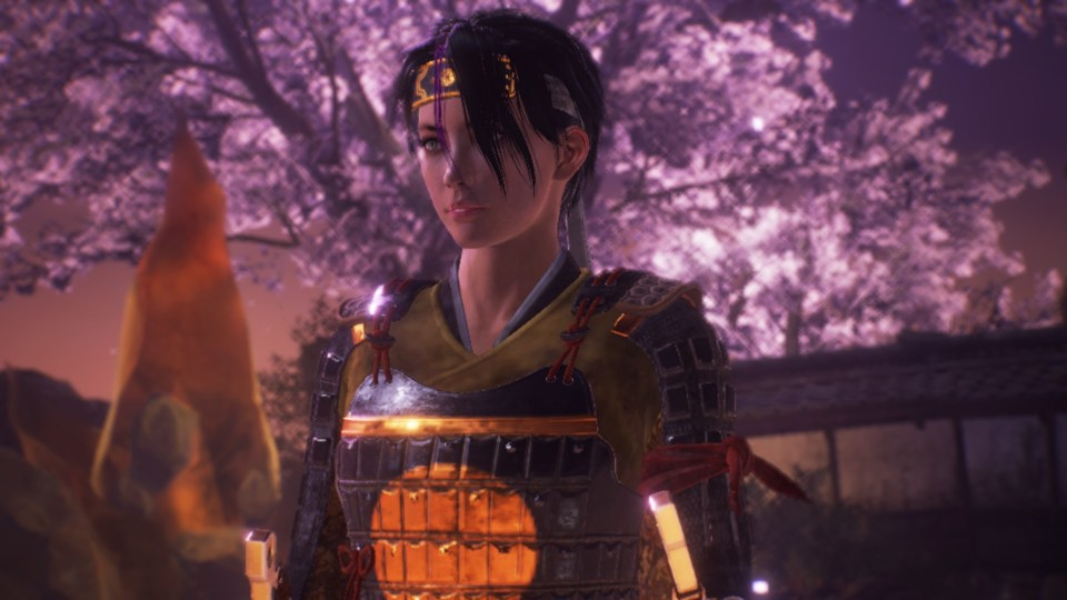 A female character wearing armour stands in the foreground, in the background there is a building and a cherry blossom tree