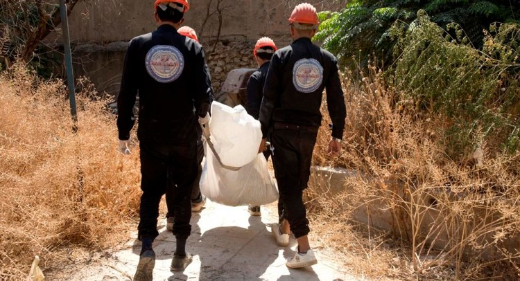 In this Saturday, Sept. 7, 2019 photo, first responders remove a body at the site of a mass grave in Raqqa, Syria. First responders said they have pulled nearly 20 bodies out of the latest mass grave uncovered in Raqqa, the Syrian city that was the de facto capital of the Islamic State group. It is the 16th mass grave in the city, and officials are struggling with a lack of resources needed to document and one day identify the thousands of dead who have been dug out. (AP Photo/Maya Alleruzzo)