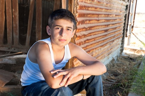 bigstock Boy Sitting In Old Barn 22182569