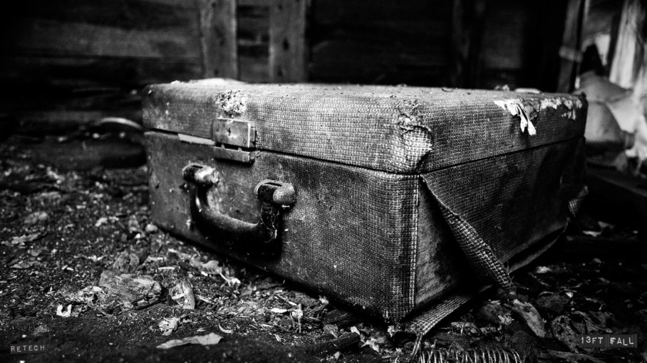 Black and white photo of a tattered suitcase in a burned out building