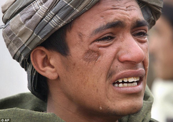 An Afghan youth mourns for his relatives, who were allegedly killed by the U.S. service member