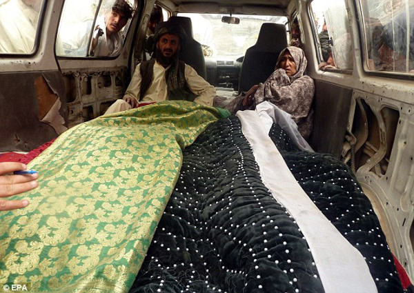 Relatives sat in shock in a van also carrying the bodies of their kin wrapped in blankets