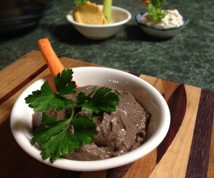 Plate with baba ganouj with garnish of parsley and a stick of carrot