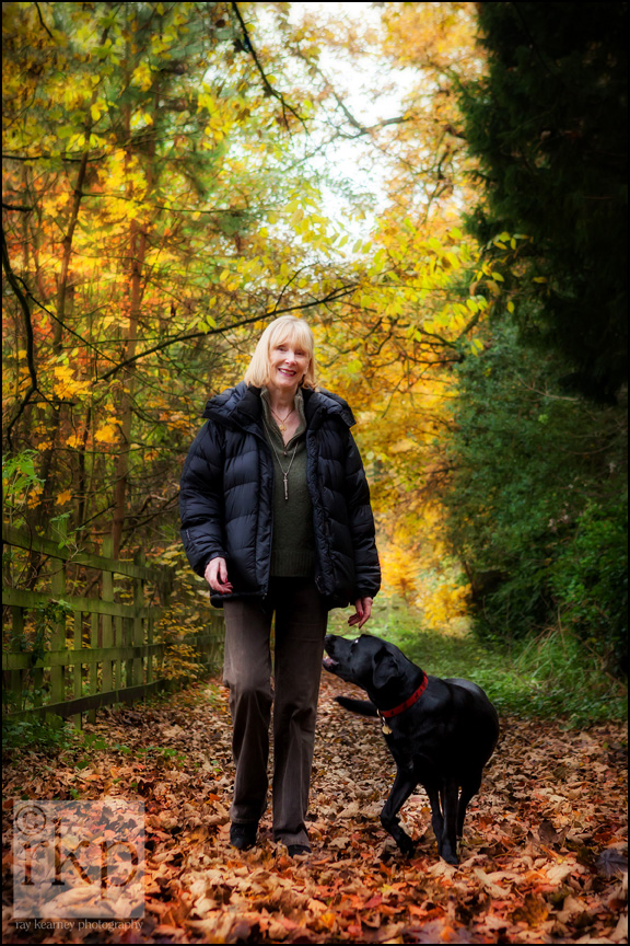 Black Labrador and woman walking in autumn leaves by Ray Kearney Photography