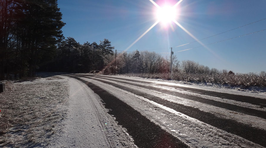 An ice covered paved road is illuminated by the bright winter sun in Connecticut