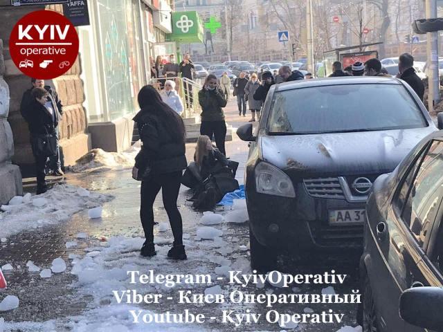 В центре Киева на девушку упала огромная глыба льда: ее пытаются спасти пешеходы (фото)