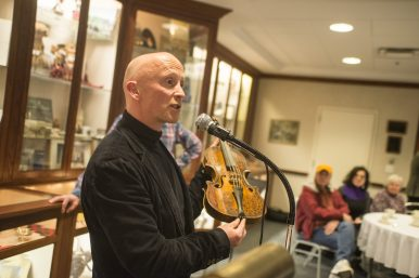 David Hopes the head of collections and interiors for the National Trust for Scotland, talks about the history of the Gregg Violin during a special concert at Caledonia Senior Living and Living Care in North Riverside on Jan. 29. (Alex Rogals | Staff Photographer)