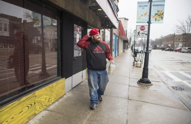 """Jason Tripodi, of Homewood, walks out of Burger Antics in Brookfield with different homemade sauces on March 18. Tripodi is a former employee who worked at the restaurant back in 2018. """"I came out here from Homewood to support these guys during this time,"""" Tripodi said.   ALEX ROGALS/Staff Photographer"""