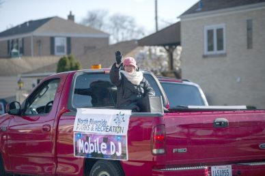 North Riverside Parks and Rec employee Julie O'Brien waves to residents along 11th Avenue on April 13 from the bed of the Mobile DJ truck, which takes to village streets every Monday at 5 p.m. | Alex Rogals/Staff Photographer
