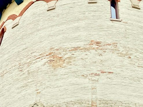 The mineral coating on the upper portion of the Riverside water tower has been flaking off the surface, along with pieces of the brick face, since it was applied in 2004. Structural improvements made inside the tower at the time are causing the problem, and a fix will be expensive. (Bob Uphues/Editor)