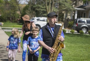 """Jim Vonesh, accompanied by his wife, Tara, and his children, Jaden and Alia, parade down Herrick Road in Riverside during one of his recurring """"sax walks"""" on May 7. (Alex Rogals/Staff Photographer)"""