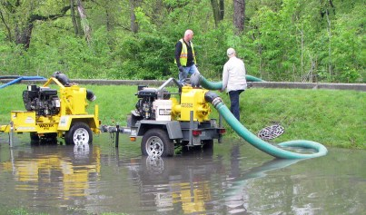 Riverside public works employees pumped out standing water from Groveland Avenue on May 18, after surcharging sewers flooded the street the night before. (Photo by Allen Goodcase)
