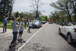 Residents and neighbors fill the sidewalk while waving and cheering as Maxx Kusper is brought home on May 16, during a parade at the corner of Washington and Arden Avenues in Brookfield. (Alex Rogals/Staff Photographer)