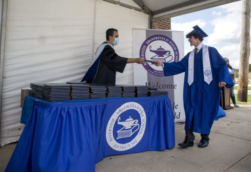 RB Principal Dr. Freytas gives out the diplomas the graduates on Friday, May 29, 2020, during RBHS graduation ceremony outside of the school in Riverside. | ALEX ROGALS/Staff Photographer