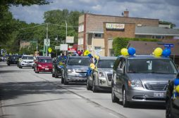 Graduates cheer from their cars on Saturday, May 30, 2020, during Komarek School's graduation parade along 26th Street in North Riverside. | ALEX ROGALS/Staff Photographer