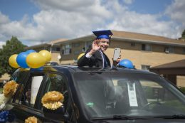 Komarek School eighth-graders wave from their vehicles to well-wishers lining a parade route from the school to Village Commons before a graduation ceremony at Veterans Park on May 30. | Alex Rogals/Staff Photographer