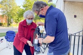 Dorothy Ball holds a lantern while it's lit by Deacon David Brencic to be carried to the second bonfire at St. Louise Church during Holy Guardian Angels Parish's Pentecost vigil.