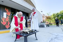 Father Denis Condon lights the bonfire for the Holy Guardian Angels Parish Pentecost vigil at St. Barbara Church in Brookfield on May 30.