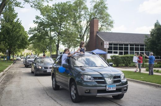 Students cheer from their cars on Friday, May 29, 2020, during a car parade for Hollywood Elementary School in Brookfield. (Alex Rogals/Staff Photographer)