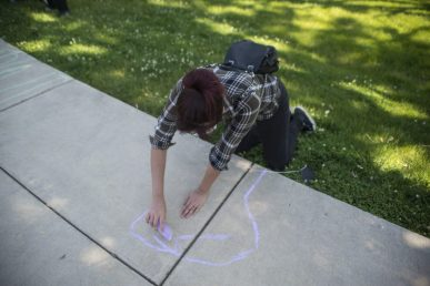Samantha Villarreal, of North Riverside, chalks the sidewalk on Saturday, June 6, 2020, during a Black Lives Matter protest at Kiwanis Park in Brookfield. | ALEX ROGALS/Staff Photographer