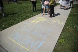 Demonstrators chalk the sidewalks on Saturday, June 6, 2020, during a Black Lives Matter protest at Kiwanis Park in Brookfield. | ALEX ROGALS/Staff Photographer