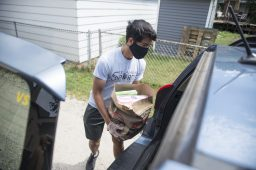 Narayan Sharma, of Elmhurst, loads up groceries in a car on Aug. 15, at the Share Food Share Love food pantry in Brookfield. (ALEX ROGALS/Staff Photographer)