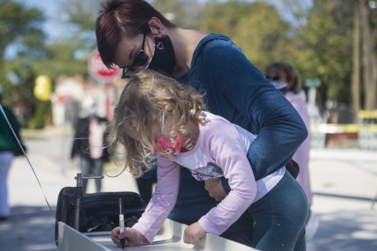 Brookfield resident Carolyn Nielsen, left, holds up her daughter, Julianne Nielsen,4, to sign a steel I-beam that will become a permanent part of the village's new library during a topping off ceremony on Sept. 19. (Alex Rogals/Staff Photographer)