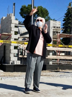 """Within reach: Brookfield Public Library Board President Dianne Duner illustrates just how high the hurdles to a new facility seemed for more than a decade during remarks at the library's """"topping off"""" ceremony on Sept. 19. (Bob Uphues/Editor)"""