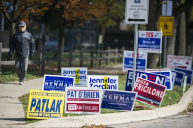 A pedestrian approaches the early voting site at Brookfield Village Hall, festooned with campaign signs, on Saturday, Oct. 24 during what has been a record-setting early voting period. (Alex Rogals/Staff Photographer)