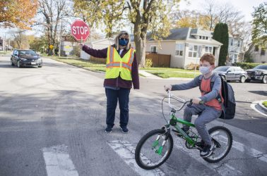 Brookfield crossing guard Michelle Luce holds up a stop sign as a student safely crosses the street at Hollywood and Washington avenues on Nov. 2, outside of Hollywood Elementary School in Brookfield. (Alex Rogals/Staff Photographer)