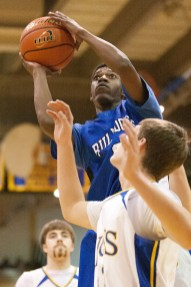 Over the top: Riverside Brookfield's Eric Loury shoots over a Lyons Township defender.