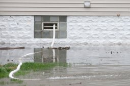 A pump works hard to flush water out of a basement on Forest Avenue in Brookfield.