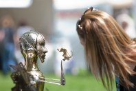 A fest goer leans in for a closer look at a mixed media sculpture by artist James Eichorst.