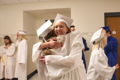 Kaija Bole hugs friend Andie Krug as the two see other for the first time in graduation robes.