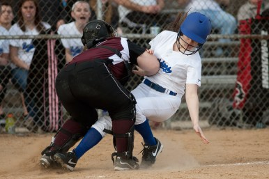 The Morton catcher blocks the plate as Riverside-Brookfield's Kate Kosner, right, tries to score. The ball got past the catcher and Kosner was able to score in the Bulldogs' 8-7 win Friday. (David Pierini/staff photographer)