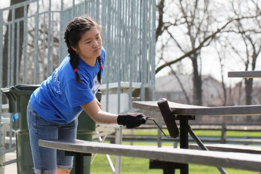A Riverside-Brookfield High School student paints benches at Kiwanis Park in Brookfield as part of the high school's Day of Service in 2013. (Photo courtesy of RBHS)