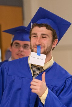 Seniors were instructed to stand by their names in two hallways and then bring the name tag with them to hand over to an announcer. Michael Meade found his name. (David Pierini/staff photographer)