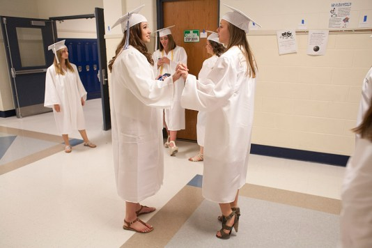 Denise Raga, left, and Caitlyn Moravecek hold hands as graduating seniors begin to lineup by their names. (David Pierini/staff photographer)