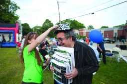 Library employee Marty Blank got a little help after a gust of wind blew off his party hat while he was distributing brochures.