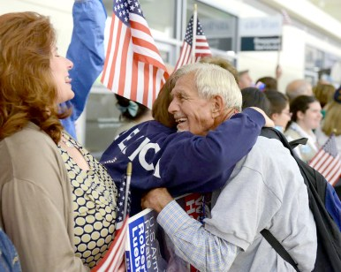 Brookfield's Bob Luebben gets a hug from one of the more than two dozen friends and neighbors who went to Midway Airport to welcome him home from his Honor Flight on July 2. (Photo courtesy of Honor Flight Chicago)